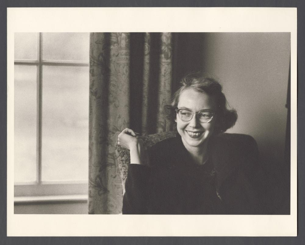 old black and white photo of a woman sitting in a chair smiling, wearing glasses, mid 20th century