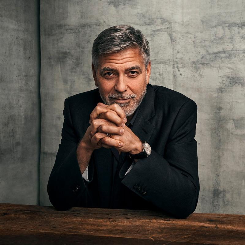 george clooney in dark suit clasping hands, looking into the camera