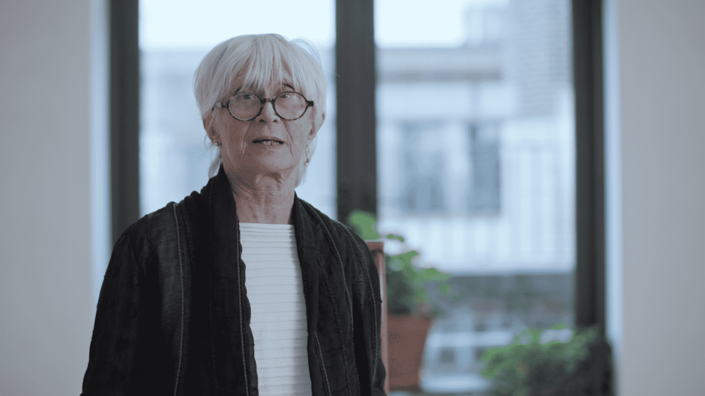 twyla tharp, white straight hair and round black glasses in a black jacket and white shirt