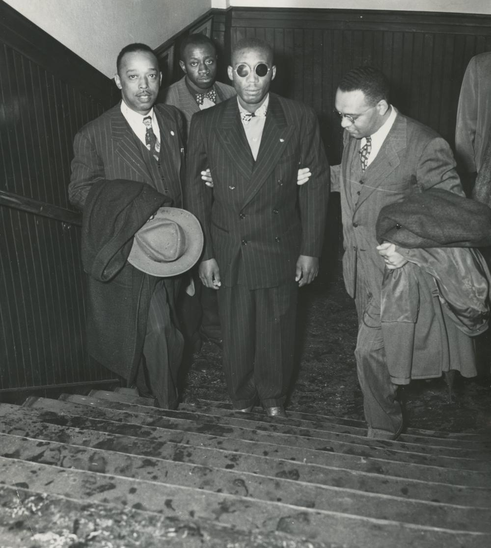 black and white image of men leading another blind man with dark glasses up a staircase. all but the blind man wear suits and carry long coats.